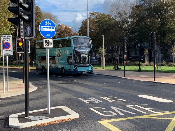 """The words 'bus gate' are painted on the road. To the left of the road markings there's a blue, circular signpost next to a set of traffic lights, the sign shows a bicycle, bus and the word taxi"""