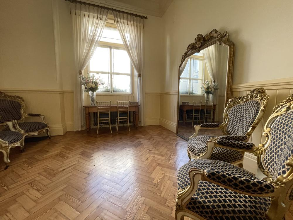 The Ante Room. A room with 6 chairs, wooden floor, large mirror and desk by the window.