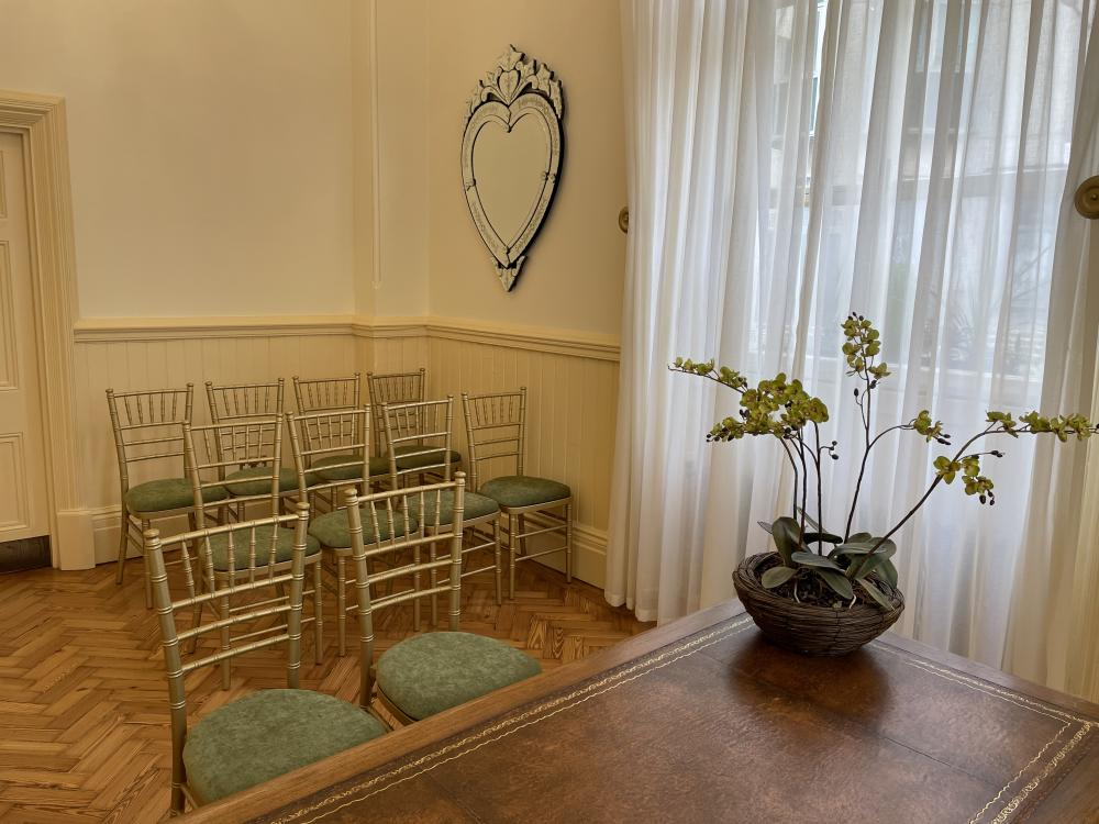 Fitzherbert Room. A room with 10 chairs and a table. Heart mirror on the wall. Floor to ceiling window