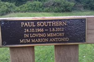 """close up of memorial plaque in the centre of the top panel a wooden bench"""