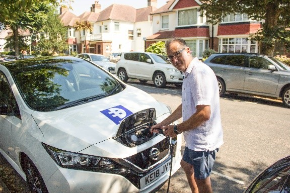 Cllr Pete West charging an electric car on a residential road.
