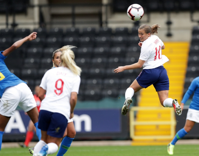 England player Kirby jumps to head the ball