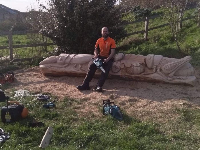 Daniel Cordell sits on his carved bench