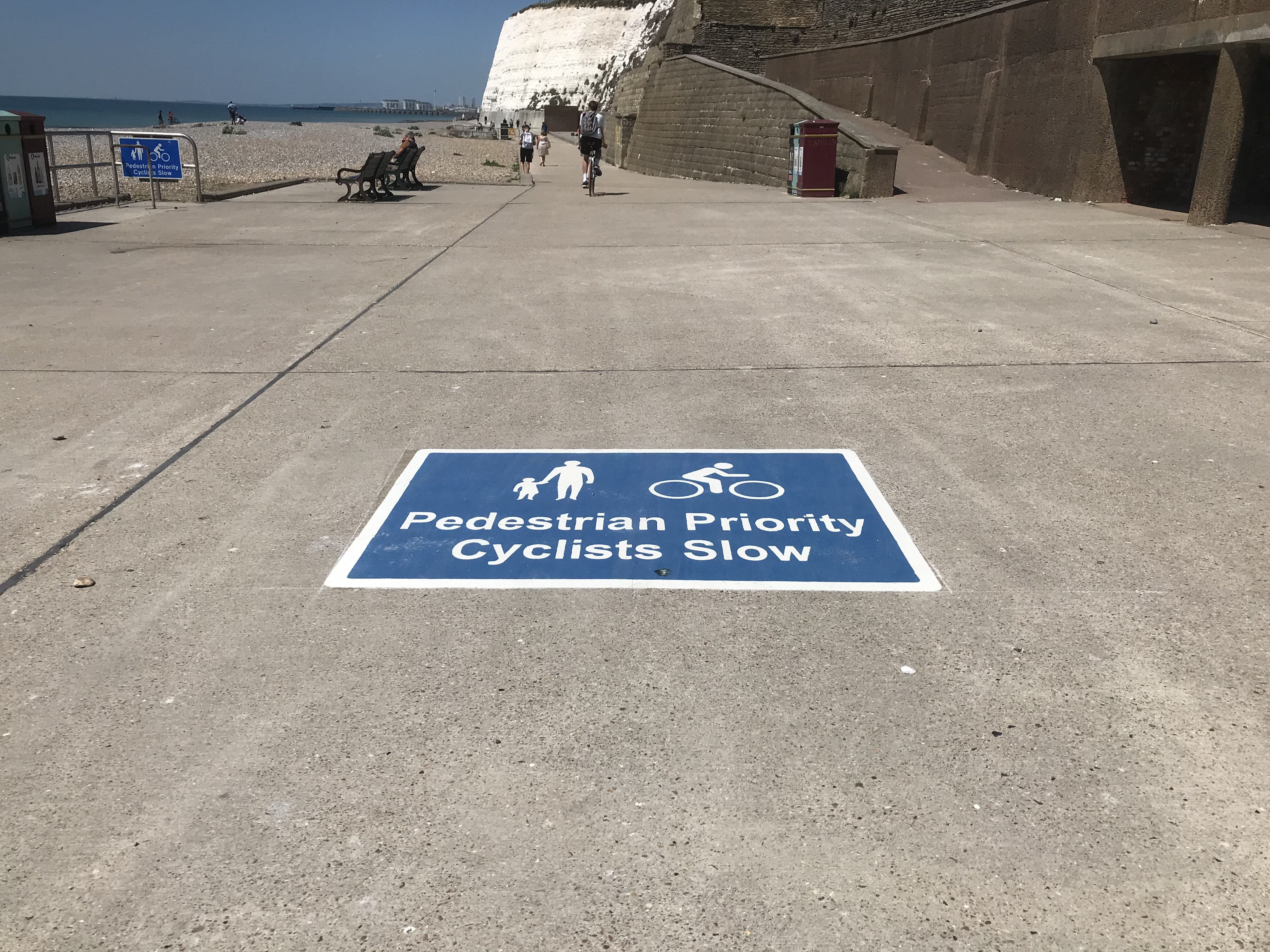 Signage with the words Pedestrian Priority Cyclists Slow on the ground
