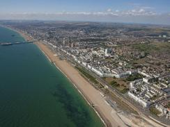 Panoramic aerial view of Brighton & Hove, with the sea on the left and buildings on the right.