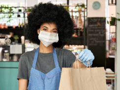 Woman working in a coffee shop wearing a mask and an apron, holding out a paper bag