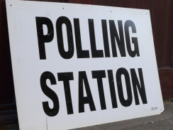 Photo of a white sign with the words 'polling station' written in black writing