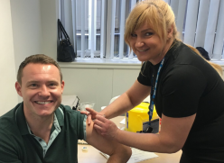 Man getting a flu vaccination from a nurse