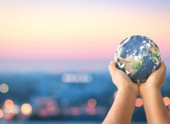 Child's hands holding a globe against a sunset
