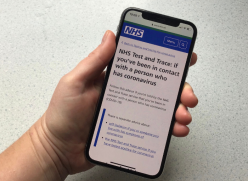 Photo of a hand holding a mobile phone showing the NHS  Test and Trace website