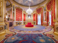 The recently restored Saloon at the Royal Pavilion, showing the intricately patterned carpet, scarlet and gold curtains and chandelier hanging from a ceiling painted with a blue sky and clouds.