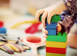 Photo of a child's hands playing with building blocks