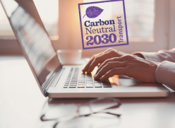 Person's hands typing on a laptop keyboard. The laptop is on the desk. A logo is above the hands with an illustration of a leaf and the words: Carbon Neutral 2030, transport
